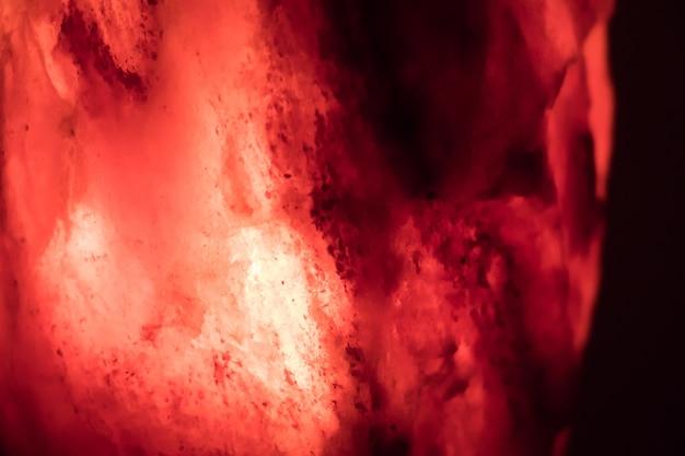 Primer plano de una lámpara de sal roja sobre un fondo oscuro, perfecto para móviles