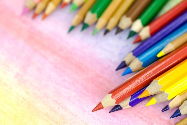 Primer plano de lápices de colores grandes sobre un fondo de color con lápices de colores