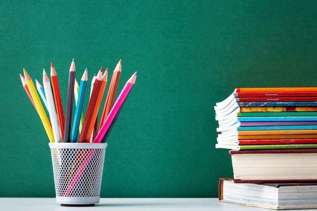 Primer plano de lápices de colores con libros de texto