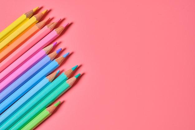 Primer plano de lápices de colores sobre una pared rosa con espacio de copia