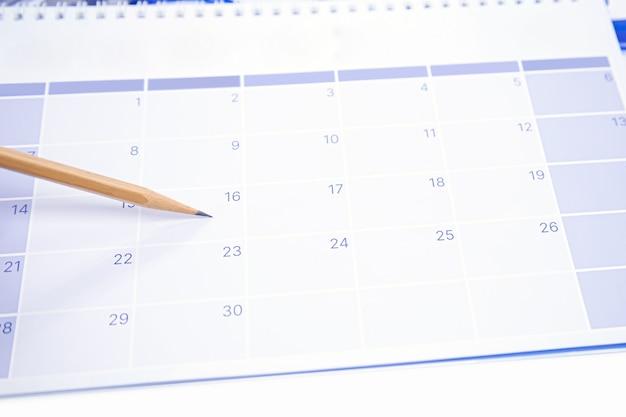 Primer plano de un lápiz en el calendario de escritorio en blanco.