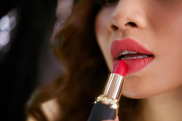 Primer plano de lápiz labial tocando los labios femeninos rojos regordetes