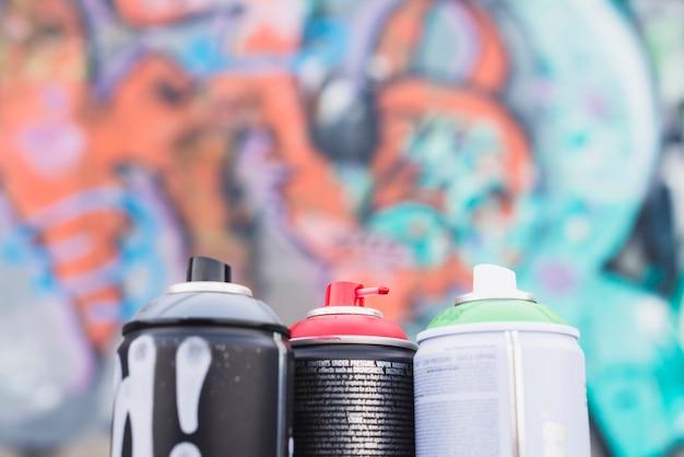Primer plano de latas de aerosol frente a la pared de graffiti borroso