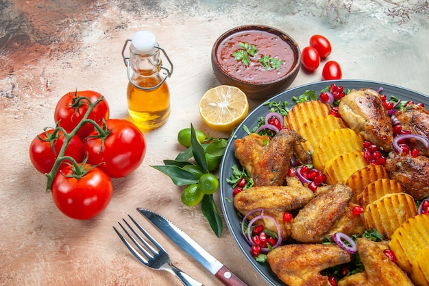 Primer plano lateral plato de pollo de alitas de pollo patatas hierbas tenedor cuchillo tomate aceite salsa de limón
