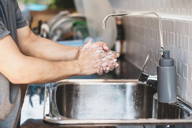 Primer plano de lavado de manos de hombre asiático con agua del grifo en la cocina de casa