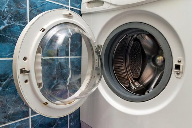Un primer plano de la lavadora abierta en el baño.