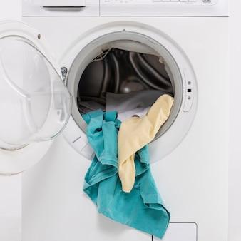 Primer plano lavadora abierta con ropa dentro
