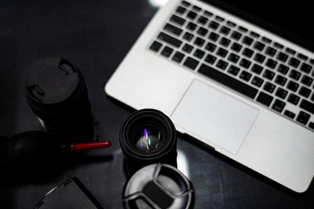 Primer plano de una lente de cámara y una computadora portátil