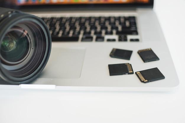 Primer plano de la lente de la cámara y tarjetas de memoria en la computadora portátil