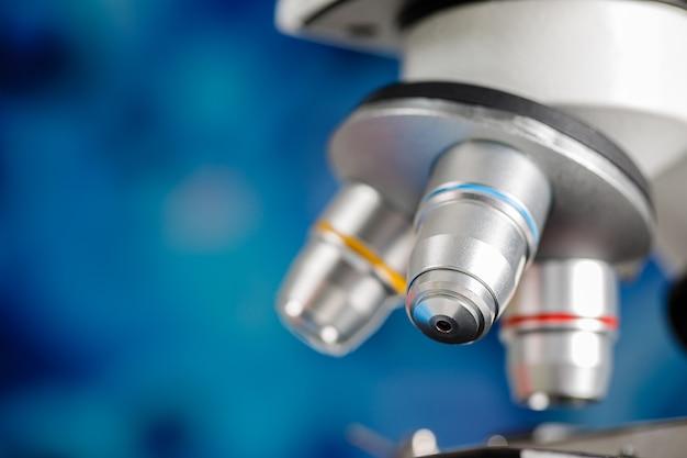 Primer plano de la lente del microscopio y el espacio de copia de fondo azul borroso colorido.