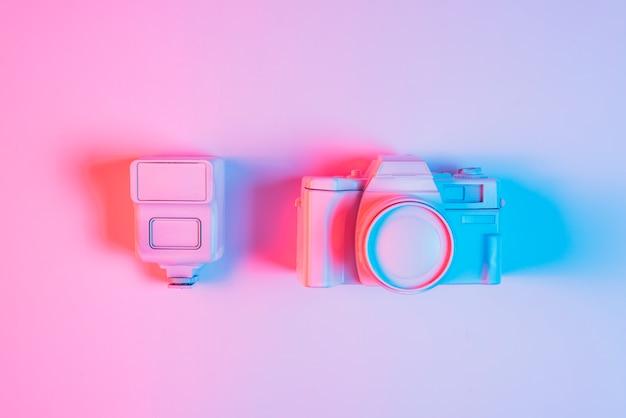 Primer plano de lente pintada con cámara vintage contra fondo rosa