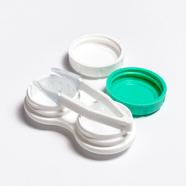 Primer plano de lentes de contacto transparentes con estuche y pinzas