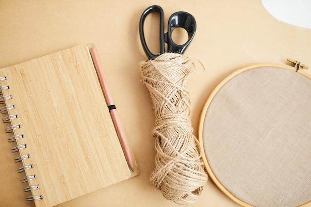 Primer plano de la libreta de notas tijeras e hilo acostado sobre la mesa de madera y preparándose para la costura