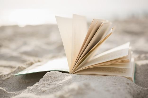 Primer plano de libro abierto sobre la arena
