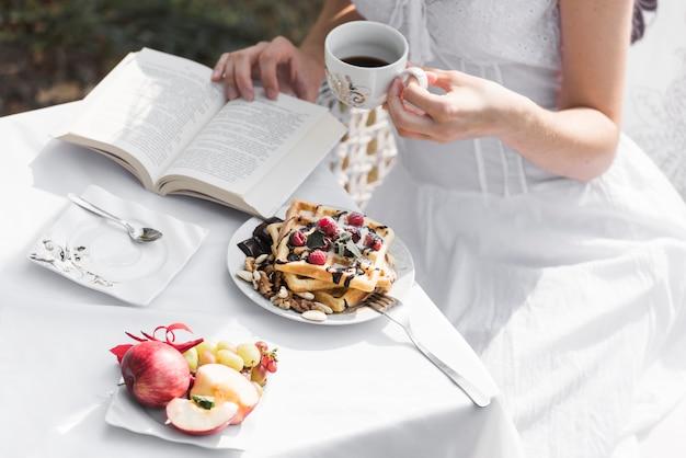 Primer plano de un libro de lectura de mujer desayunando