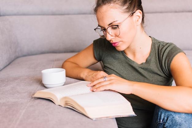 Primer plano de un libro de lectura de mujer joven con una taza de café en el sofá