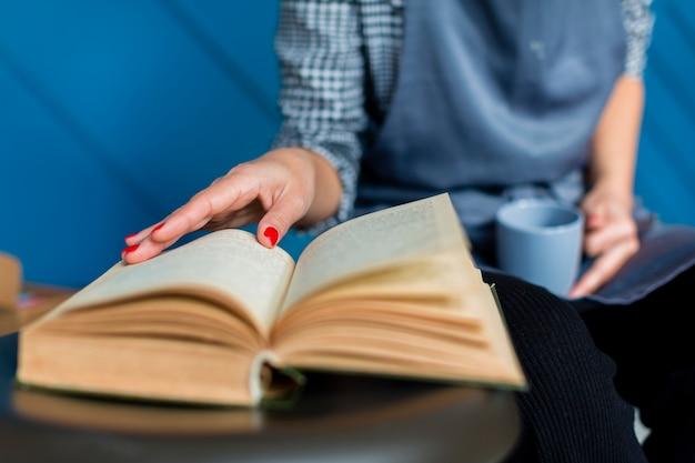 Primer plano de libro y mujer sosteniendo la taza