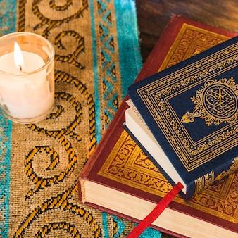 Primer plano de libros árabes cerca de vela