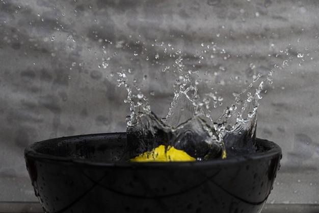 Primer plano de un limón y salpicaduras de agua en un recipiente negro bajo las luces contra una pared gris