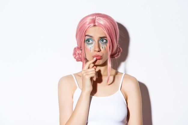 Primer plano de linda chica preocupada con peluca de fiesta rosa, mirando a la izquierda y pensando, de pie en disfraz de halloween.