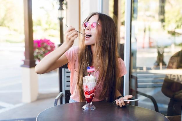 Primer plano de linda chica sentada en un café comiendo helado con cereza en la parte superior con una cuchara. ella usa top rosa y anteojos rosas. ella escucha música en su teléfono inteligente. ella esta disfrutando de su helado