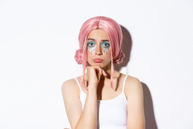 Primer plano de una linda chica triste con maquillaje de halloween y peluca rosa que parece molesta, enfurruñada mientras está de pie.