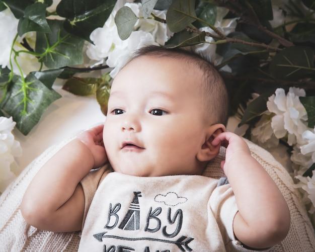 Primer plano de un lindo bebé caucásico rodeado de flores