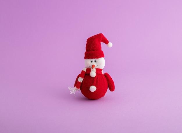 Primer plano de un lindo muñeco de nieve en la superficie púrpura