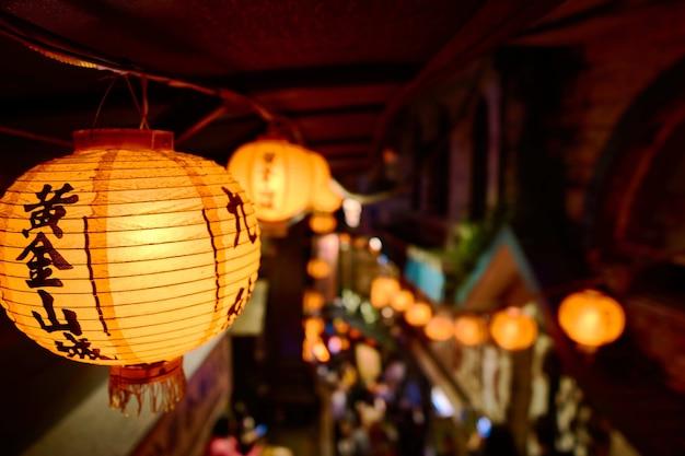 Primer plano de una linterna de papel chino con luces rodeadas por edificios