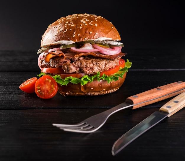 Primer plano listo para ser servido hamburguesa con cubiertos