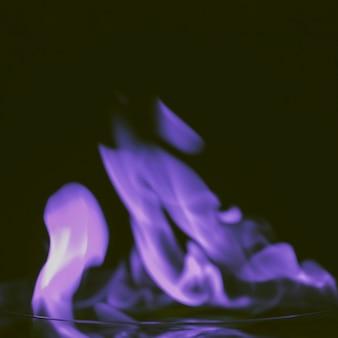 Primer plano de llamas púrpuras sobre fondo negro