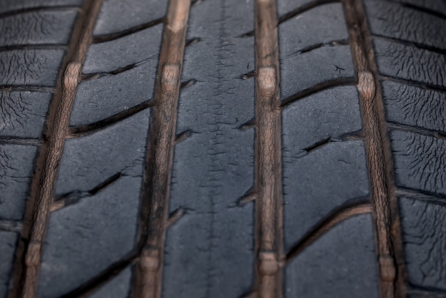 Primer plano de llantas viejas con banda de rodadura desgastada y agrietada, banda de rodadura negra resistente al desgaste, grietas grandes en llantas negras