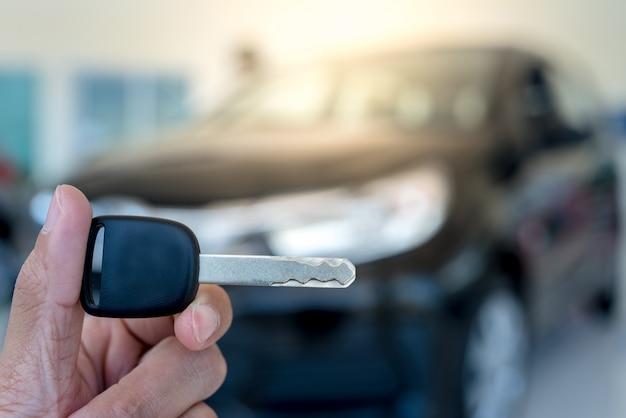 Primer plano de la llave de un automóvil: un joven sosteniendo una nueva llave del automóvil en la sala de exposición, nueva llave