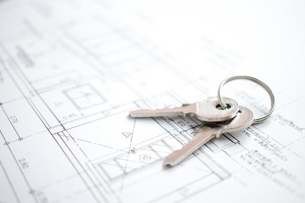 Primer plano de las llaves de la casa en papel de plano de nuevo hogar.