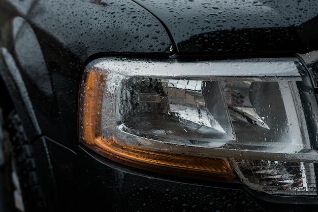 Primer plano de las luces delanteras de un coche cubierto por gotas de lluvia