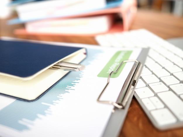 Primer plano del lugar de trabajo de negocios con teclado de computadora y documentos financieros. informe mensual con gráficos de problemas económicos. cuaderno y bolígrafo para notas. concepto de rutina de oficina