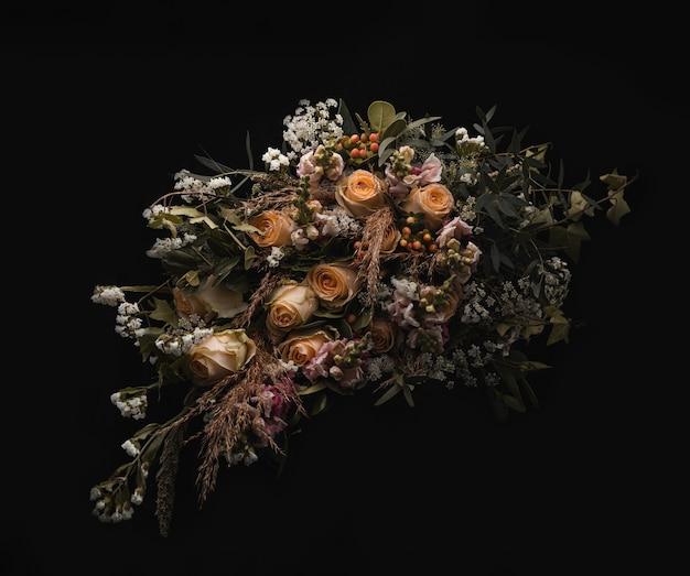 Primer plano de un lujoso ramo de rosas naranjas y marrones sobre un fondo negro