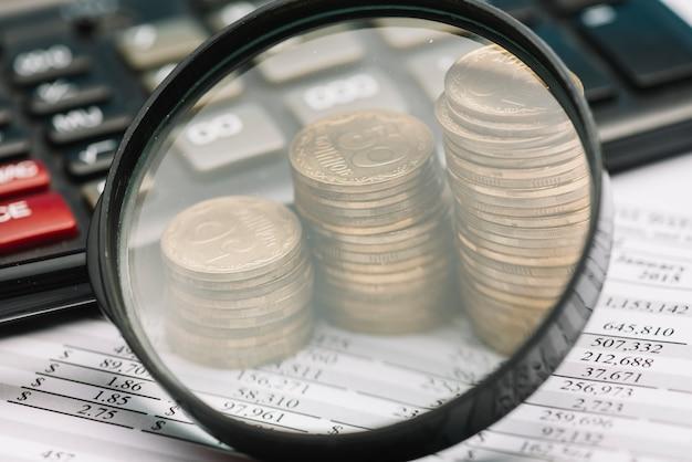 Primer plano de la lupa sobre la pila de monedas y la calculadora sobre el balance financiero
