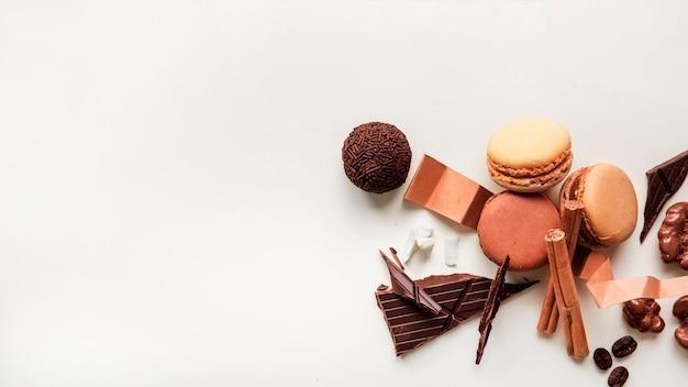 Primer plano de macarrones y bola de chocolate con ingredientes sobre fondo blanco