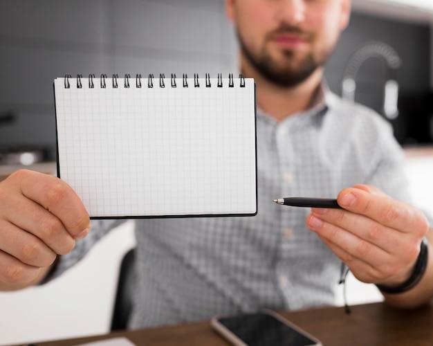 Primer plano macho adulto sosteniendo el bloc de notas