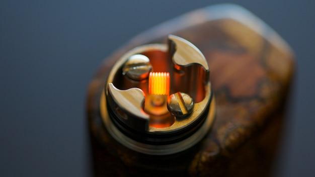 Primer plano, macro foto de prueba quemando la micro bobina simple en atomizador de goteo reconstruible de alta gama para perseguir el sabor