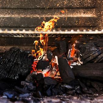 Primer plano de una madera en llamas en la parrilla de la barbacoa