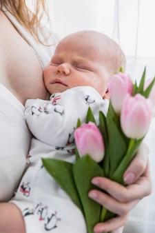 Primer plano de madre con bebé durmiendo y flores de tulipán rosa