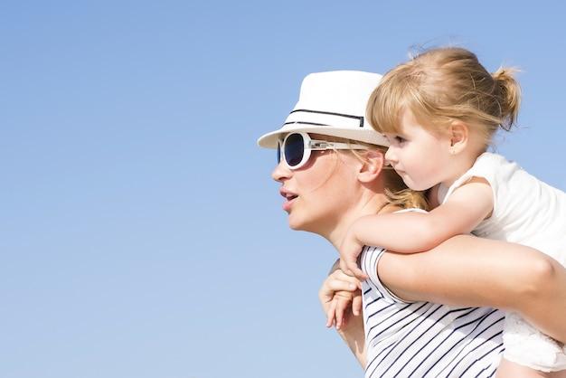 Primer plano de una madre caucásica dando un paseo a cuestas a su hija durante el día