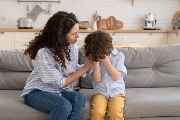 Primer plano de una madre preocupada calma a un niño llorando