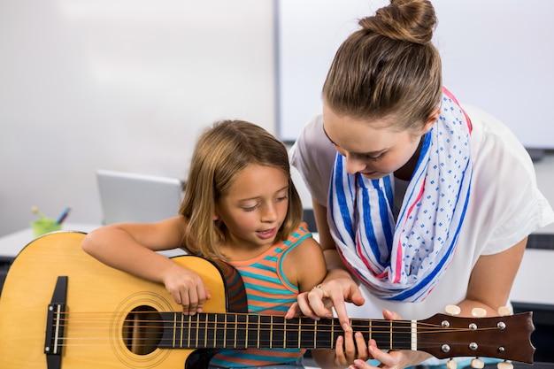 Primer plano del maestro ayudando a la niña a tocar la guitarra en el aula