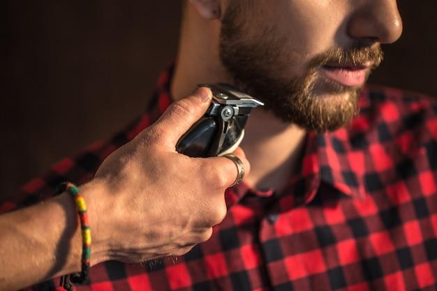 Primer plano del maestro corta el cabello y la barba de los hombres