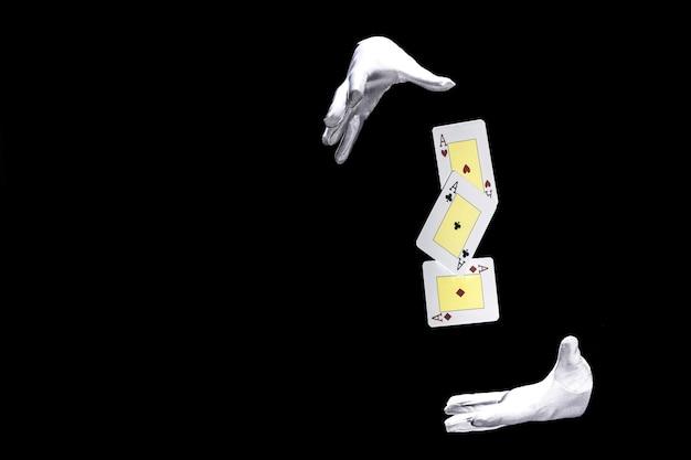 Primer plano del mago que realiza truco con naipes contra el fondo negro