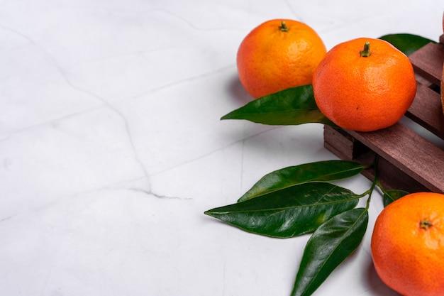 Primer plano de las mandarinas frescas y deliciosas sobre una superficie blanca