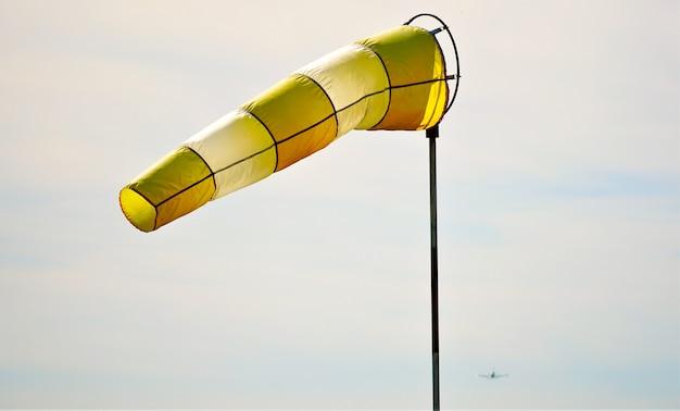 Primer plano de una manga de viento amarilla y blanca flotando en el aire durante el día